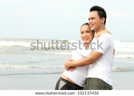 Portrait of a happy young couple hugging each other at the beach