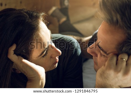 Portrait of a happy young couple looking into each other's eyes. Close-up of a man and a woman in love looking into each other's eyes in a romantic way.Concept of love, happiness and romanticism