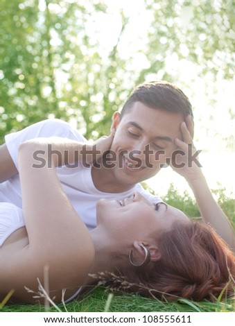Portrait of a happy young couple lying on grass in the park - Outdoor
