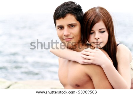 Portrait of a happy young couple together on the beach