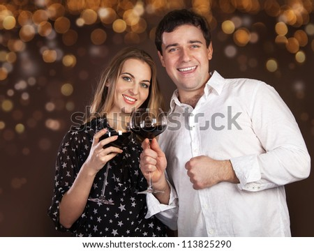 Portrait of a happy young couple with red wine on blurred lights background