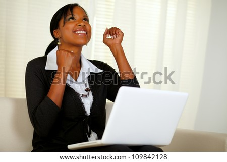 Portrait of a happy young entrepreneur woman celebrating a business victory on laptop and looking up while sitting on couch