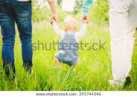 Portrait of a happy young family teaching baby to walk in the park