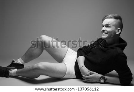 Portrait of a happy young fashionable man in trendy clothes sitting over gray background. Perfect haircut. Hipster style. Copy-space. Black and white (monochrome) studio shot