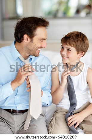 Portrait of a happy young father and his son holding necktie and looking at each other