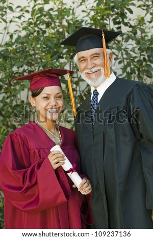 Portrait of a happy young female graduate holding certificate with dean
