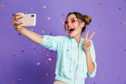 Portrait of a happy young girl with bright makeup isolated over violet background, taking a selfie under confetti shower