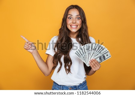 Portrait of a happy young girl with long brunette hair standing over yellow background, holding money banknotes, pointing away