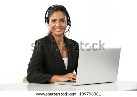 Portrait of a happy young Indian female call centre employee with a headset. Isolated on a white background. - stock photo