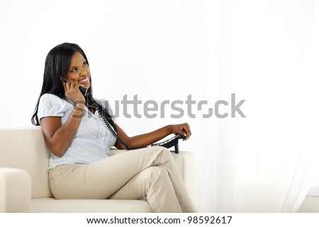 Portrait of a happy young lady talking on phone and looking up