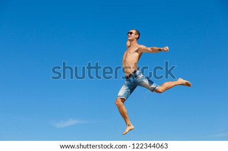 Portrait of a happy young man having fun on the beach on a summer vacation.