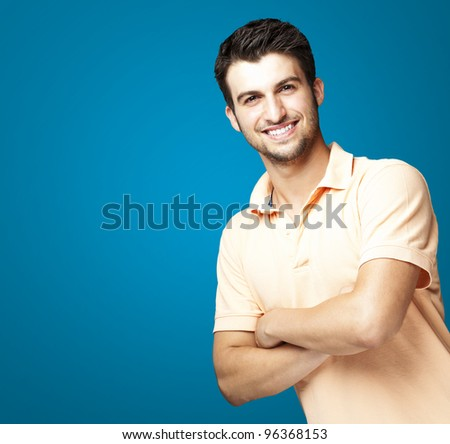 portrait of a happy young man smiling against a blue background