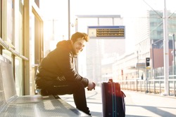 Portrait of a happy young man waiting for train at station with bag