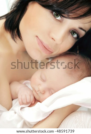 Portrait of a happy young mother holding a baby
