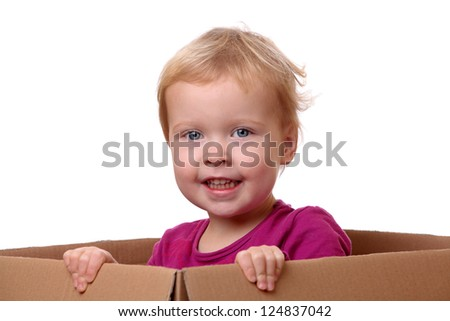 Portrait of a happy young toddler sitting in a box
