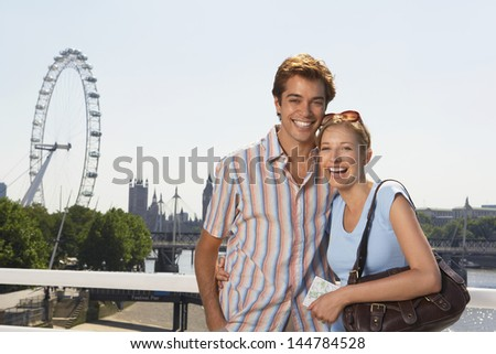 Portrait of a happy young vacationing couple against Thames River and London Eye