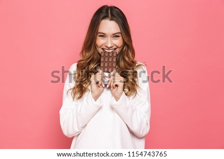 Portrait of a happy young woman biting chocolate bar isolated over pink background