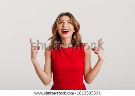 Portrait of a happy young woman dressed in red dress pointing fingers up at copy space isolated over white background