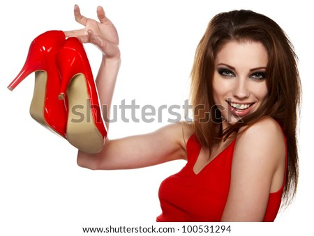 Portrait of a happy young woman holding a red shoe