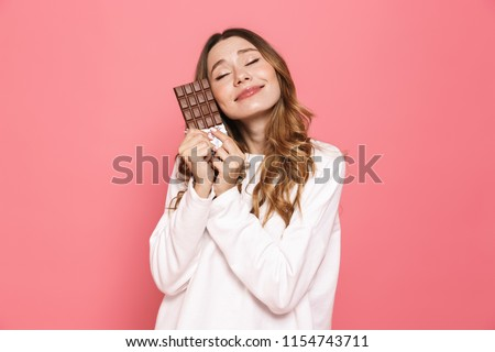 Portrait of a happy young woman hugging chocolate bar isolated over pink background #1154743711