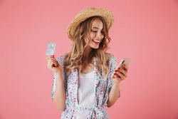 Portrait of a happy young woman in summer dress and straw hat showing plastic credit card while using mobile phone isolated over pink background