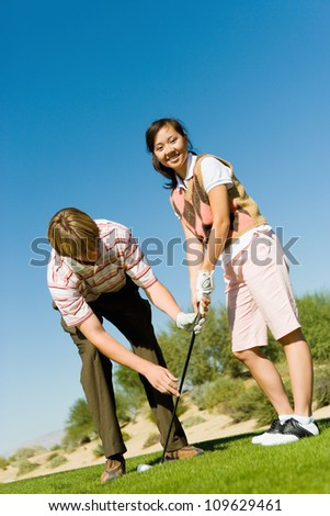 Portrait of a happy young woman learning golf from man on golf course - stock photo