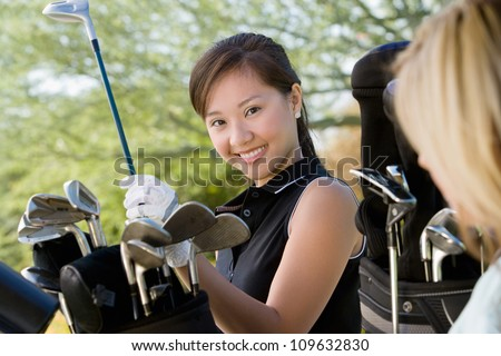 Portrait of a happy young woman picking up golf club from bag