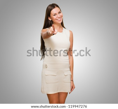 Portrait Of A Happy Young Woman Pointing At You against a grey background