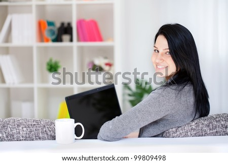 Portrait of a happy young woman sitting on sofa using laptop