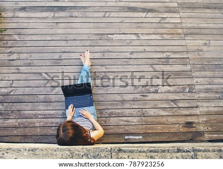 Portrait of a happy young woman sitting on the city wooden surface and using laptop computer outdoors #787923256