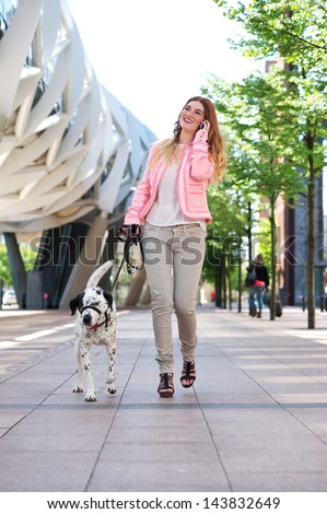Portrait of a happy young woman walking her dog and talking on cellphone in the city