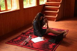 Portrait of a happy young woman with musical instrument and laptop.Girl with long hair composing music on a white sheet sitting on the floor holding a trumpet with bare legs in a wooden country house