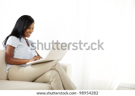 Portrait of a happy young woman working on laptop and having fun