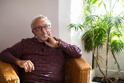 Portrait of a healthy senior man living with HIV sitting in a whicker chair