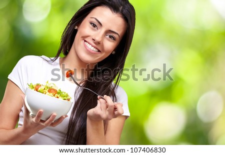 portrait of a healthy woman eating a salad against a nature background