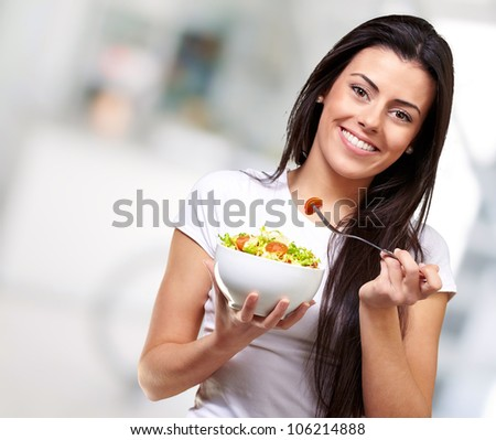 portrait of a healthy woman eating a salad indoor