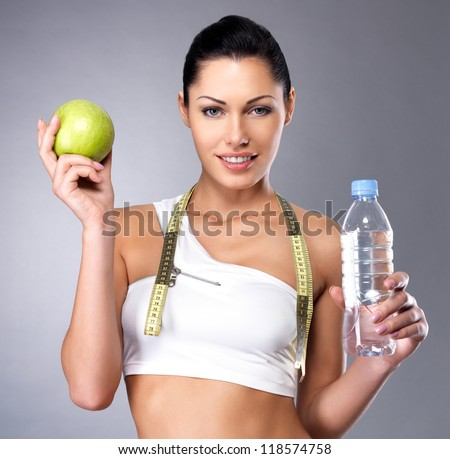 Portrait of a healthy woman with apple and bottle of water. Healthy fitness and eating lifestyle concept.