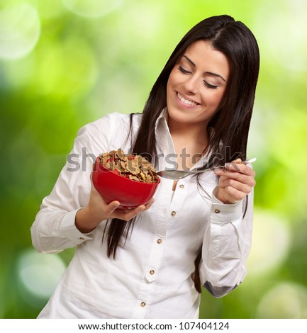 portrait of a healthy young woman eating cereals against a nature background