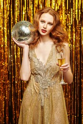 Portrait of a high fashion model woman posing in an expensive evening dress holding disco ball against a background of shiny gold curtains. Holiday fashion. Party, celebration.