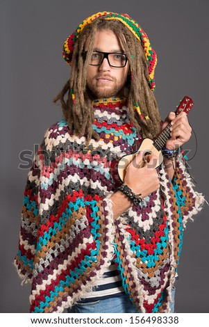 Portrait of a hippie young man playing his guitar.