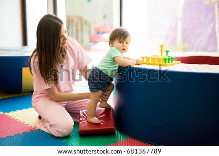 Portrait of a Hispanic baby standing and practicing maintaining balance while playing in a children therapy center