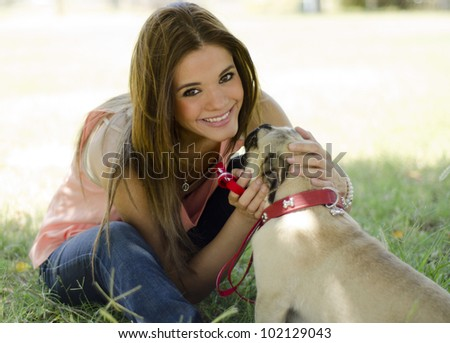 Portrait of a hispanic woman with her pug dog at the park