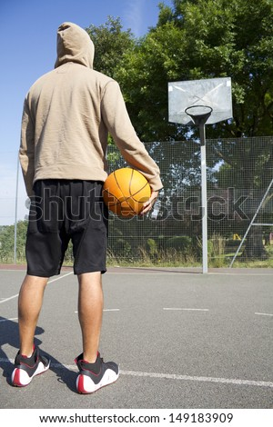 Portrait of a hooded Basketball Player facing the ring. Concept of sports challenge or competition