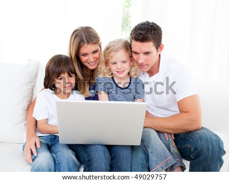 Portrait of a jolly family using a laptop sitting on sofa at home - stock photo