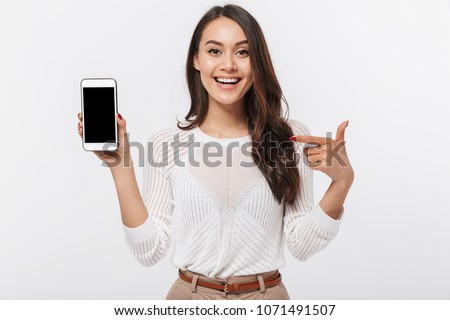 Portrait of a joyful asian businesswoman showing blank screen mobile phone isolated over white background