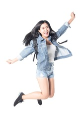 Portrait of a joyful asian woman hiker jumping in the studio while carrying a backpack, isolated on white background, 20-28 year old.