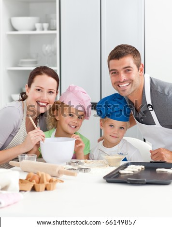 Portrait of a joyful family cooking cakes in the kitchen