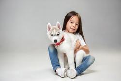 Portrait of a joyful little girl having fun with siberian husky puppy on the floor at studio. The animal, friendship, love, pet, childhood, happiness, dog, lifestyle concept