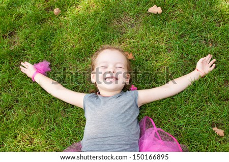 Portrait of a joyful little girl lying on grass