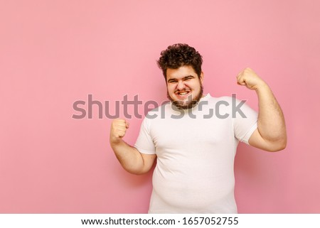 Portrait of a joyful man in a white T-shirt with overweight rejoices in victory on a pink background, looks into the camera with a happy face. Cheerful joyful fat man raised his hands up, isolated. Foto stock ©